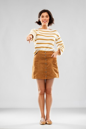 people concept - happy smiling young woman in striped pullover, short skirt and ballet flat shoes pointing to you over grey background