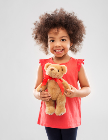 Concepto de infancia y personas - feliz niña afroamericana con osito de peluche sobre fondo gris