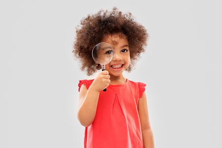 Indagine, scoperta e concetto di visione - felice piccola ragazza afroamericana che guarda attraverso la lente di ingrandimento su sfondo grigio