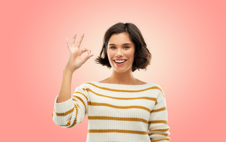 Happy smiling woman in striped pullover showing ok