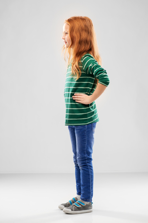 Smiling red haired girl posing in striped shirt Stock Photo