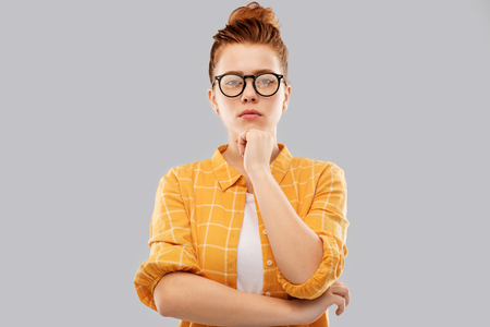 thinking redhead teenage student girl in glasses
