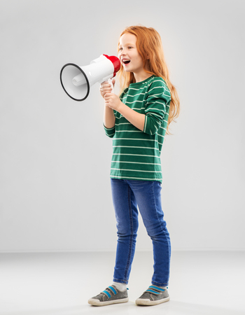 Smiling red haired girl speaking to megaphone