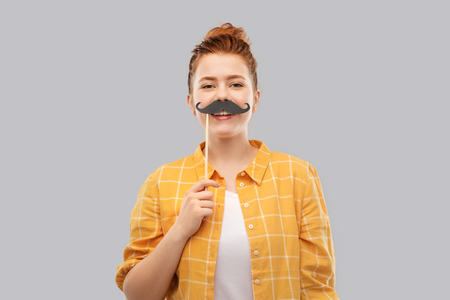 Red haired teenage girl with black moustaches