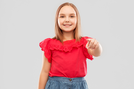 Smiling girl in red shirt pointing to you