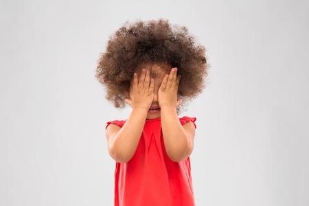 Kleines afroamerikanisches Mädchen, das ihre Augen schließt