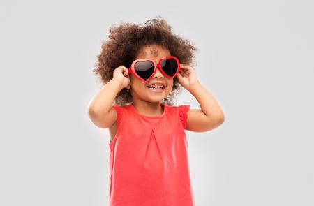 Ragazza afroamericana con occhiali da sole a forma di cuore Archivio Fotografico