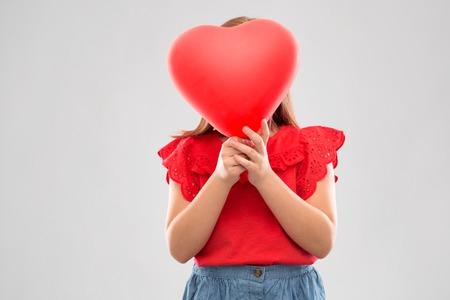Girl hiding behind red heart shaped balloon Stockfoto