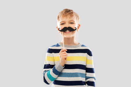 Smiling boy with black vintage moustaches