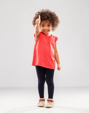 Petite fille afro-américaine montrant les pouces vers le haut
