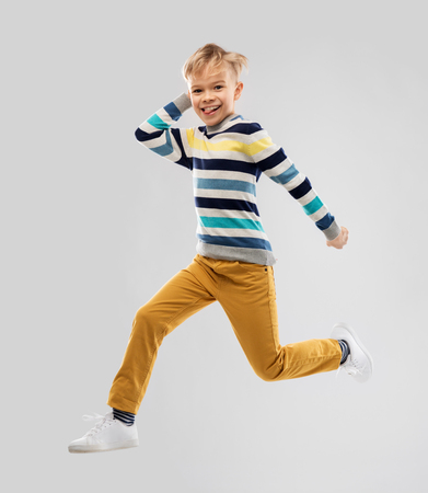 Happy little boy jumping and having fun