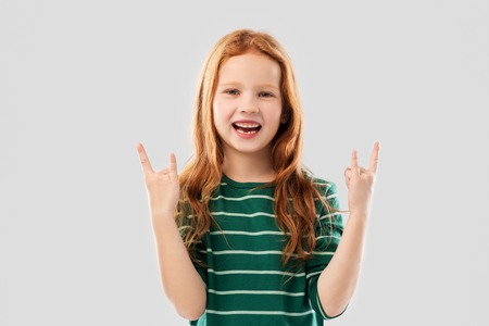 Smiling red haired girl showing rock gesture Standard-Bild - 121171021