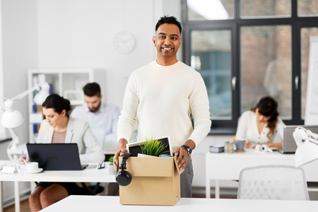 Happy male office worker with personal stuff