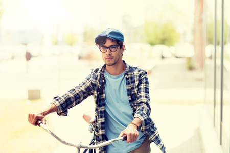 Young man with fixed gear bicycle walking in city