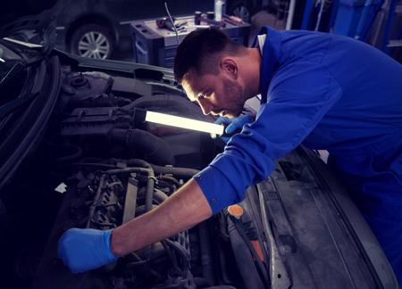 Homme mécanicien avec lampe réparant la voiture à l'atelier