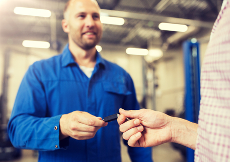 Auto mechanic giving car key to man at workshop 版權商用圖片