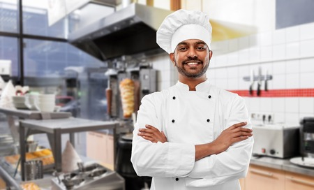 happy male indian chef in toque at kebab shop Stock Photo - 121497447