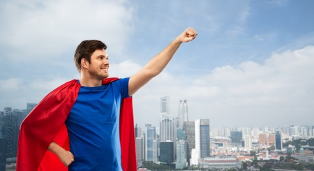 Man in red superhero cape over singapore city Stock Photo