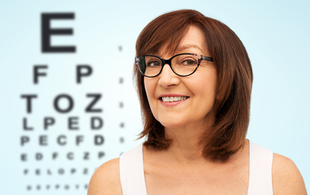 Mujer mayor feliz en gafas sobre tabla de prueba ocular