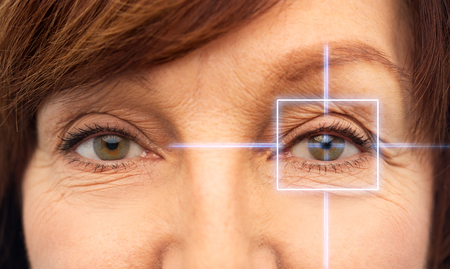 Close up of senior woman eyes with laser light Stock Photo