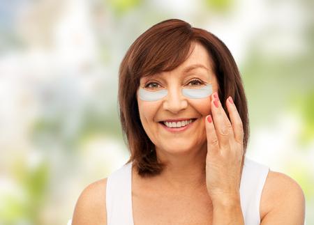 Glückliche ältere Frau mit Hydrogel unter den Augenpflastern