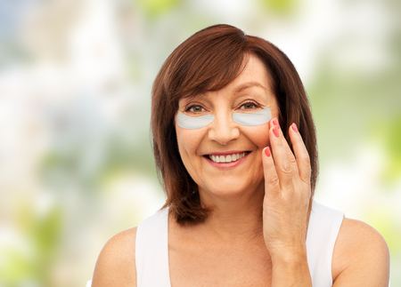 Happy senior woman with hydrogel under-eye patches