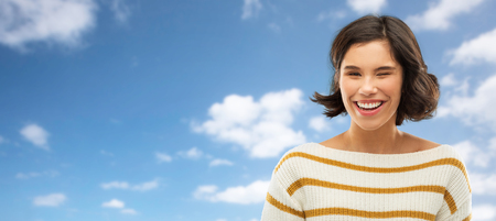 Happy smiling woman winking over blue sky 스톡 콘텐츠