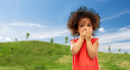 Confused African american girl covering mouth Stock Photo