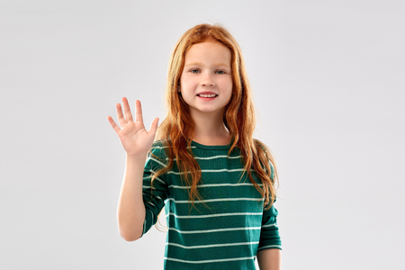 smiling red haired girl waving hand
