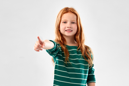 smiling red haired girl pointing to you Stock Photo