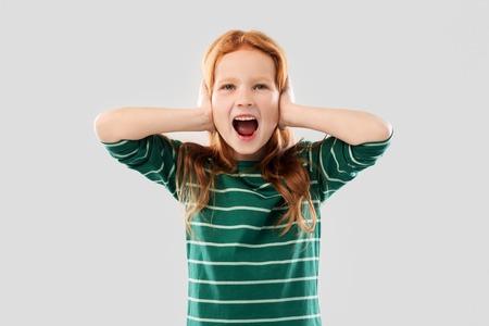 crier fille aux cheveux rouges fermant les oreilles par les mains
