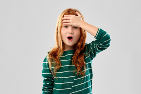 shocked red haired girl holding to her head 免版税图像