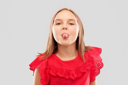 schönes Mädchen im roten Hemd, das ihre Zunge zeigt