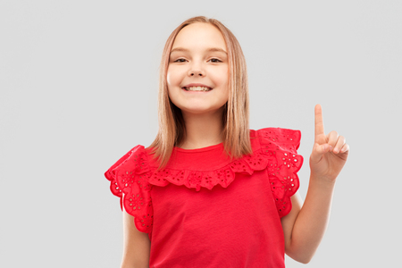 smiling girl in red shirt pointing finger up 版權商用圖片