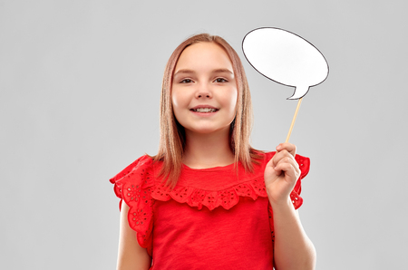 smiling girl in red holding blank speech bubble