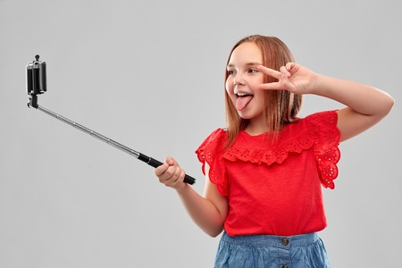 girl taking picture by smartphone on selfie stick 스톡 콘텐츠