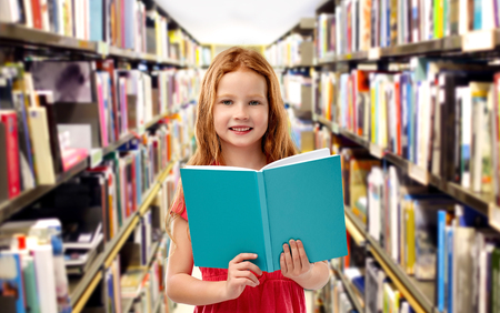 smiling red haired girl reading book at library