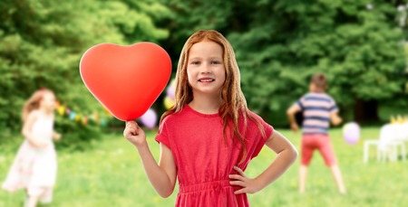 smiling red haired girl with heart shaped balloon Фото со стока