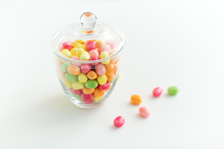 glass jar with candy drops over white background