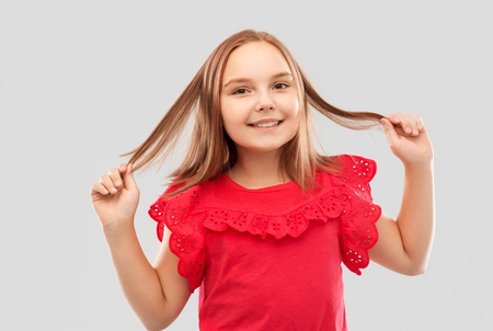 happy girl in red shirt with holding hair strands