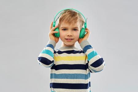 smiling boy in headphones listening to music
