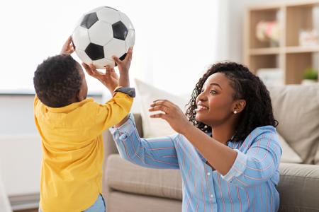 madre y bebé, juego, con, pelota del fútbol, en casa Foto de archivo