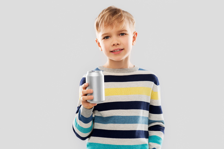 portrait of little boy with soda can drink