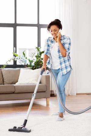 Afroamerikanerin mit Staubsauger zu Hause Standard-Bild