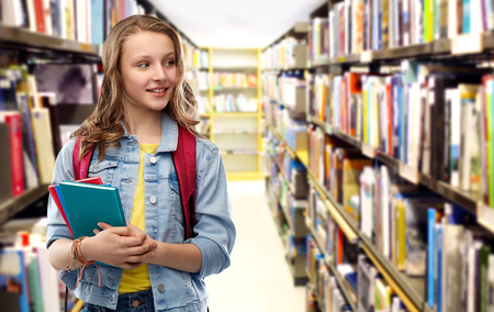 Happy smiling teenage student girl with school bag