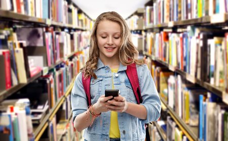 Teen student girl with school bag and smartphone Stok Fotoğraf