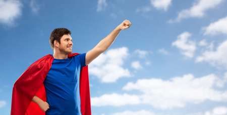 A man in red superhero cape over sky background Stock Photo