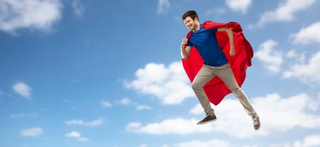 A man in red superhero cape flying over sky Фото со стока