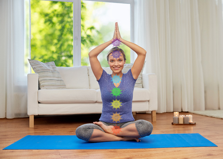 A woman in lotus pose doing yoga with seven chakras Standard-Bild