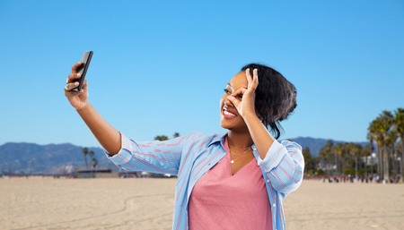 African American woman taking selfie by smartphone Stock Photo